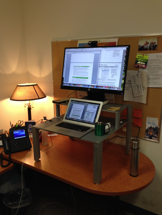 office desk with homemade wooden structure raising a laptop and screen up to standing height